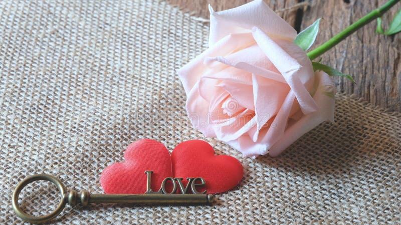 与爱形状钥匙的美丽的橙色桃红色玫瑰在两红色缎心脏 浪漫Valentine&#x27的软的口气;s天 免版税库存照片