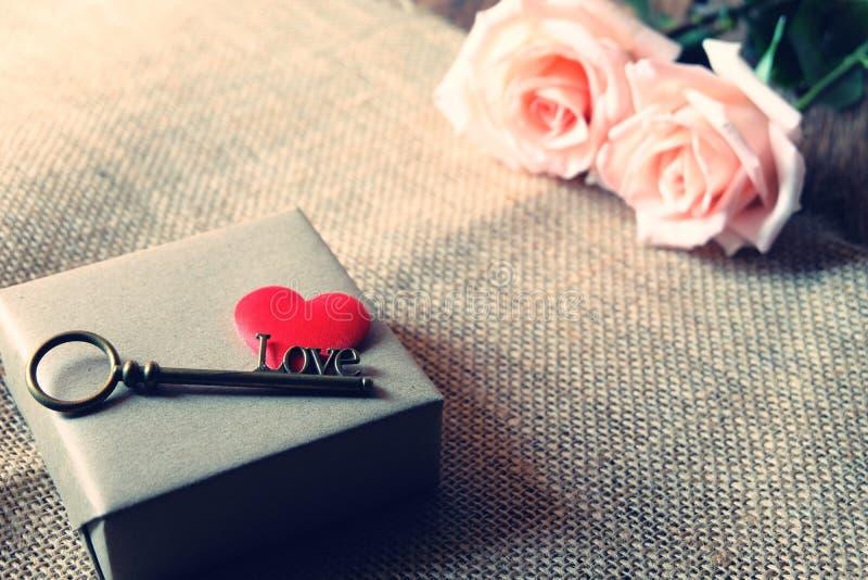 与爱形状钥匙的美丽的橙色桃红色玫瑰在两红色缎心脏 浪漫Valentine&的x27软的口气;s天 免版税库存照片