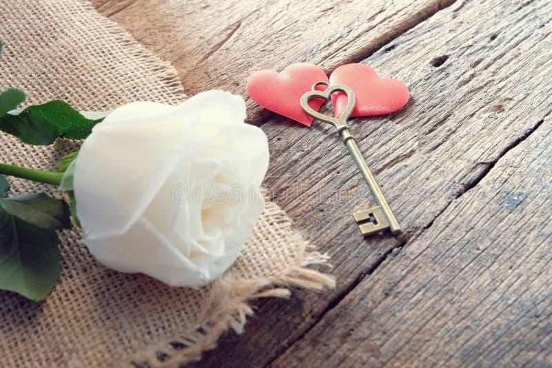 与爱形状钥匙的美丽的纯净的白色玫瑰在两红色缎心脏 浪漫Valentine&的x27软的口气;s天 免版税库存照片