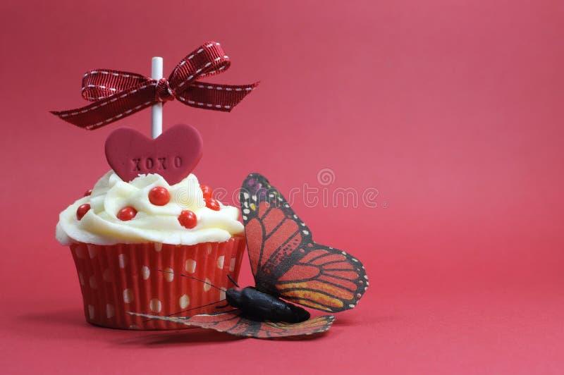 与爱心脏的红色题材在红色背景的杯形蛋糕和蝴蝶 库存照片