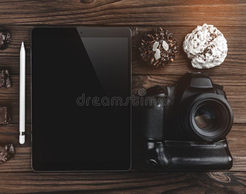 与片剂、专业照相机和巧克力饼干的工作区在木桌上 在视图之上 免版税库存图片