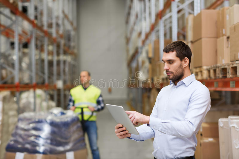 与片剂个人计算机的商人在仓库 库存图片
