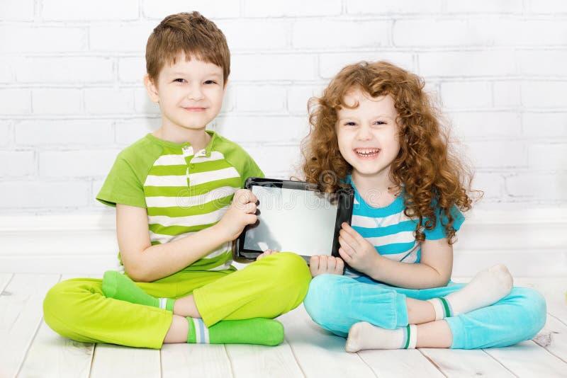 与片剂个人计算机的孪生男孩和女孩 库存照片