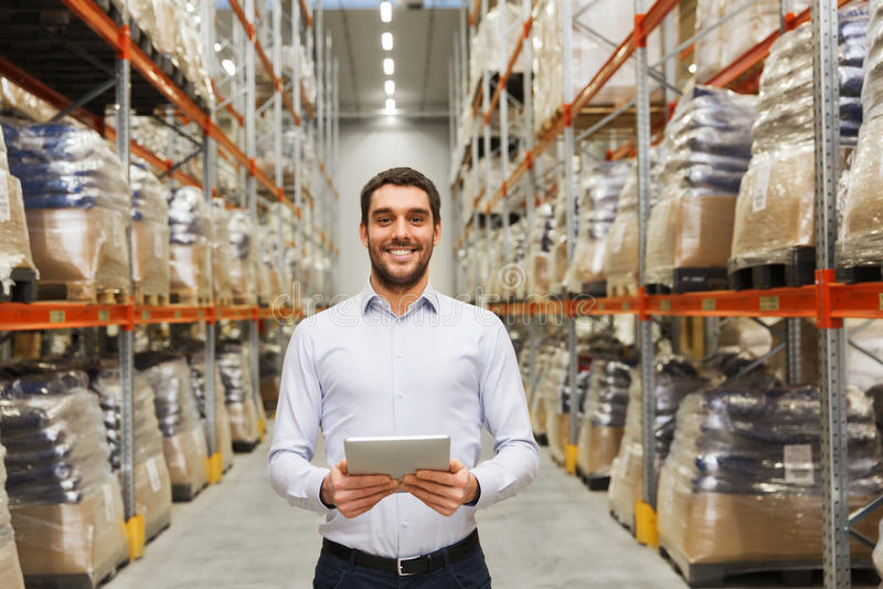 与片剂个人计算机的愉快的商人在仓库 免版税库存图片