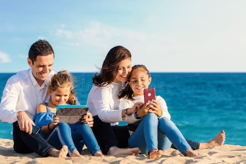 与片剂和智能手机一起的愉快的年轻家庭消费质量时间 库存图片