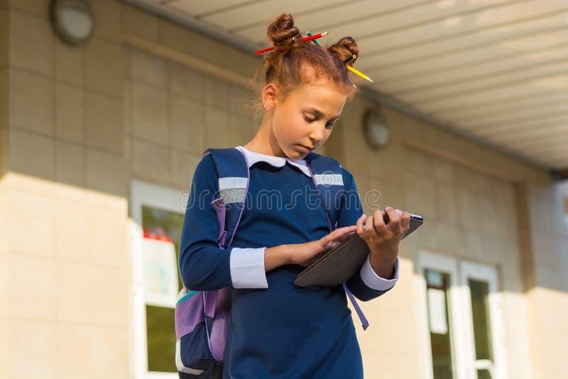 与片剂的女孩立场在学校附近和读 一个女孩在学校 库存照片