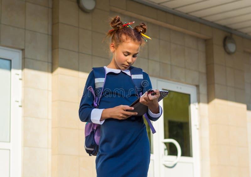 与片剂的女孩立场在学校附近和读 一个女孩在学校 库存图片