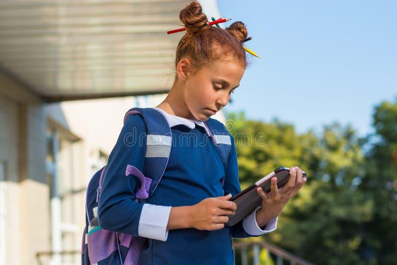 与片剂的女孩立场在学校附近和读 图库摄影