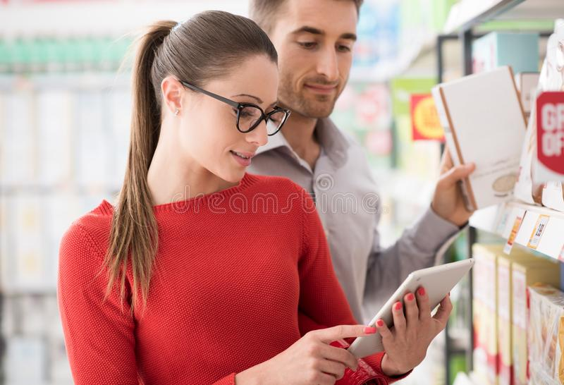 与片剂的年轻夫妇购物 库存图片