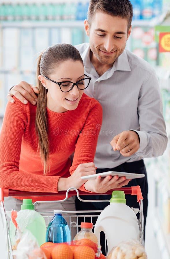 与片剂的年轻夫妇购物 图库摄影