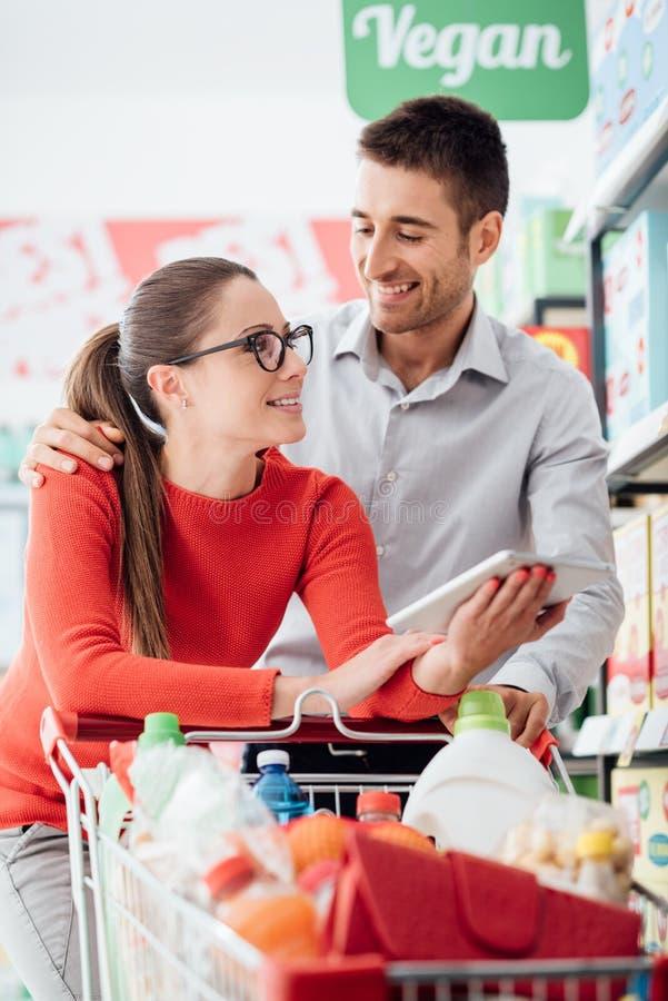 与片剂的年轻夫妇购物 免版税图库摄影