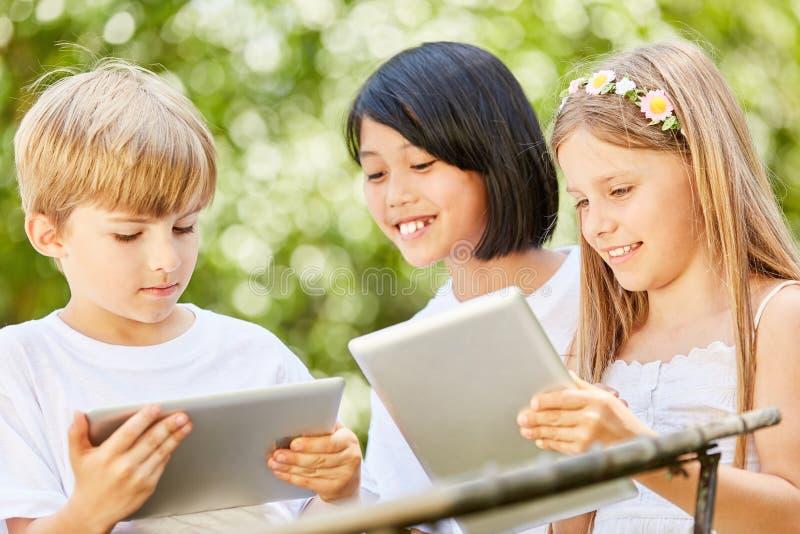 与片剂计算机的三个孩子一起学会 免版税库存照片