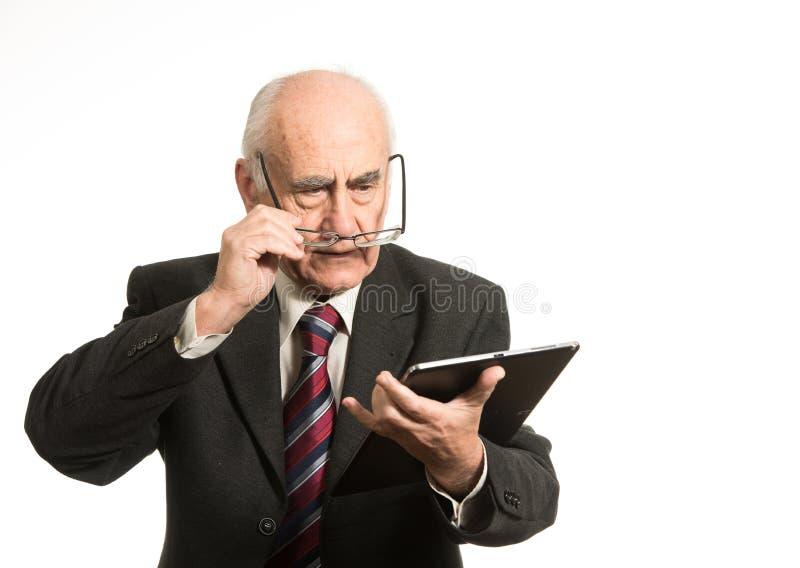 与片剂计算机的老商人 免版税库存图片