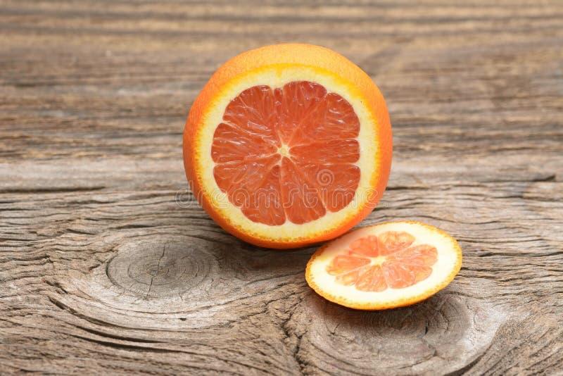 与片式的葡萄柚在一张木表 库存照片