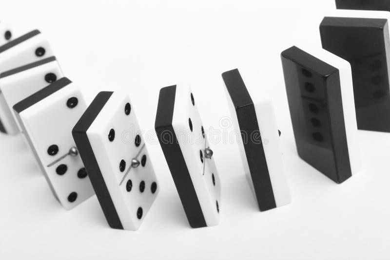 与片断的多米诺比赛在白色背景 黑色,白色 免版税图库摄影