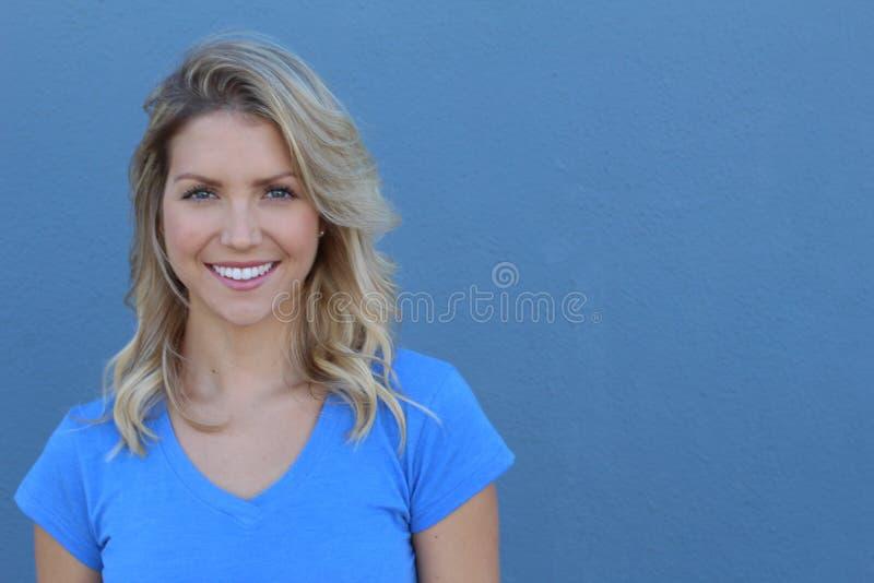 与牙的兴高采烈的少妇演播室画象微笑 女性模型被隔绝的画象与长的金发和蓝眼睛的 免版税图库摄影