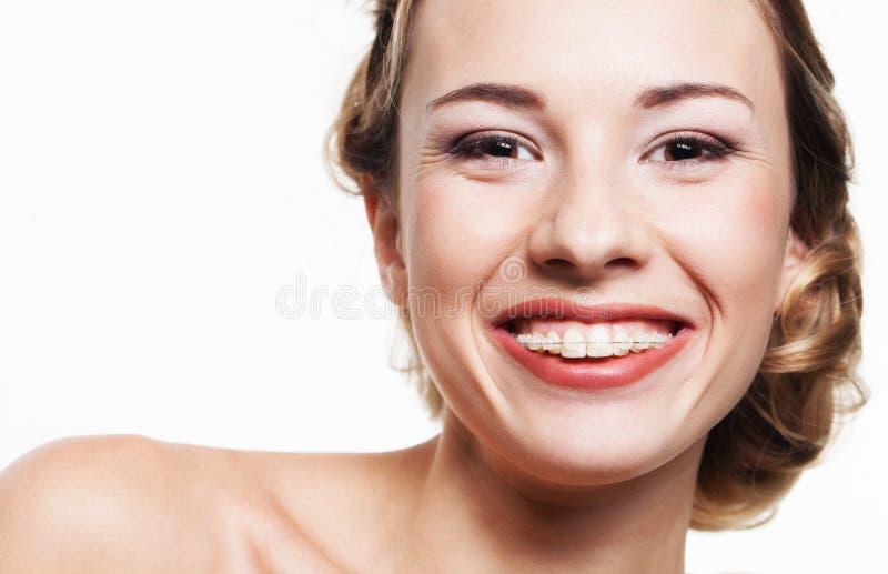 与牙齿括号的微笑 免版税库存图片