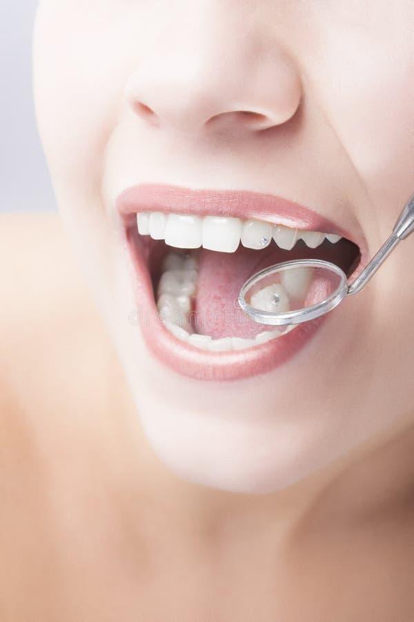 与牙医镜子的健康妇女嘴特写镜头 图库摄影