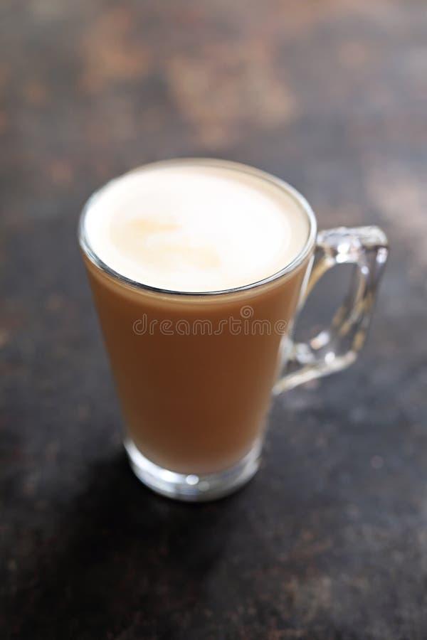 与牛奶泡沫透明玻璃杯子的平的加奶咖啡 库存照片