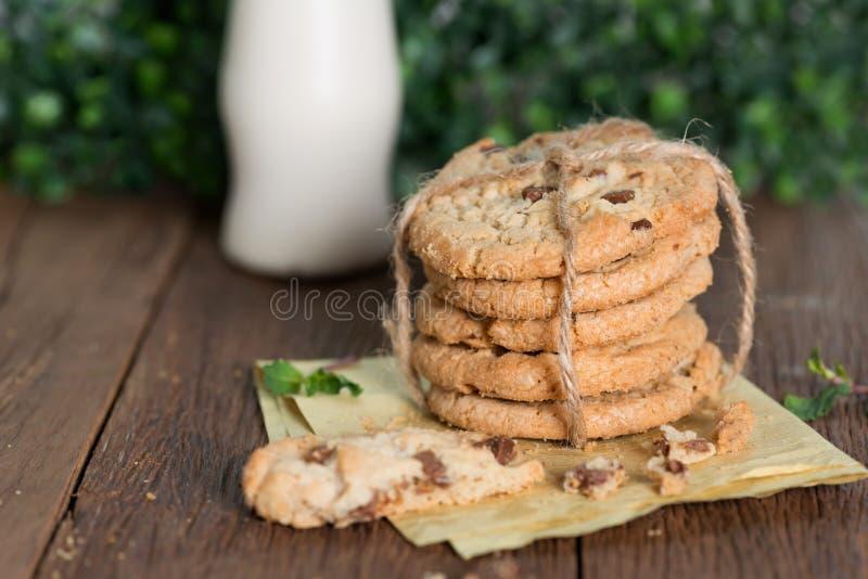 与牛奶瓶的被堆积的巧克力曲奇饼在木桌上 免版税图库摄影