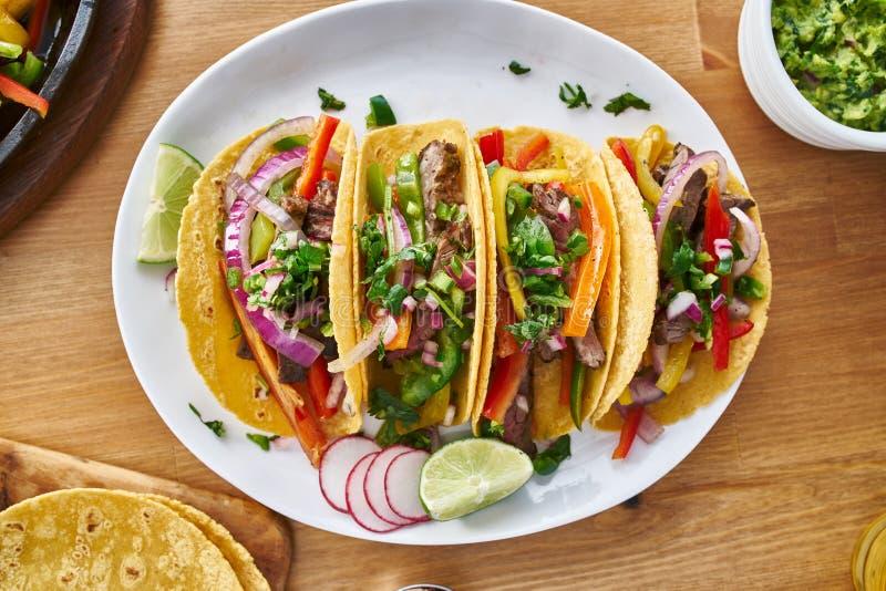 与牛肉法加它装填的鲜美墨西哥炸玉米饼服务与辣调味汁和鳄梨调味酱捣碎的鳄梨酱在平的被放置的构成 库存图片