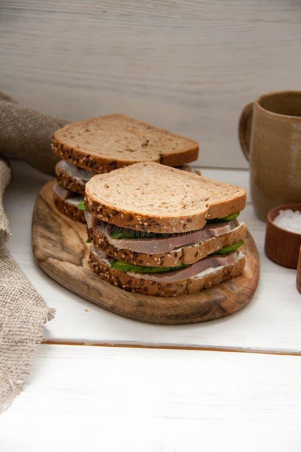与牛舌肉,新鲜的黄瓜和乳脂干酪的早餐三明治 免版税库存照片