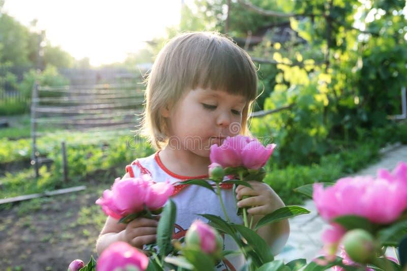 与牡丹花的小女孩画象 免版税库存照片