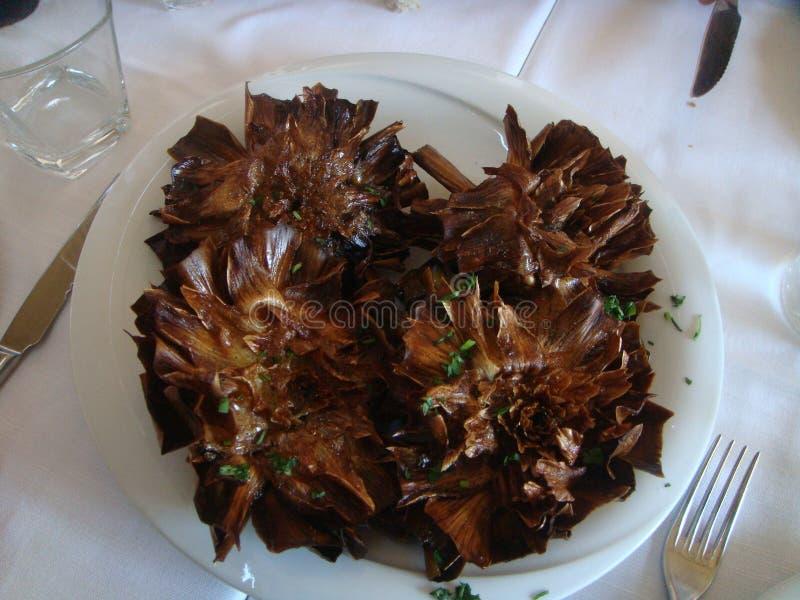 与犹太朝鲜蓟的名字,一个罗马传统盘的油煎的朝鲜蓟,服务在餐馆 罗马 意大利 库存图片