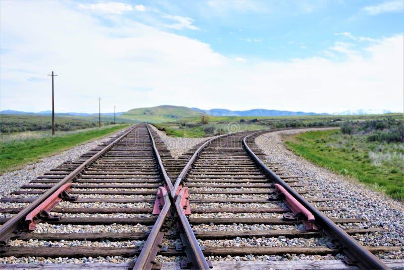 与狂放的西部山的分流的火车轨道在背景中 免版税库存照片