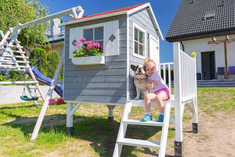 与狗的女孩画象在美丽的庭院房子 免版税库存照片