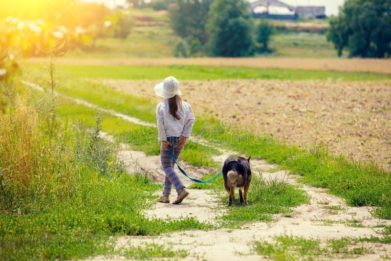 与狗的小女孩步行 免版税库存照片