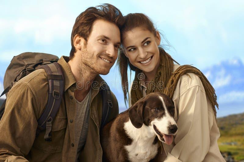 与狗的愉快的夫妇远足 库存图片