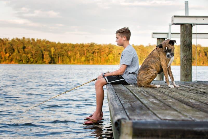 与狗的男孩渔在湖的船坞 图库摄影