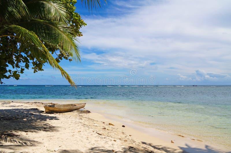 与独木舟的热带沙滩 库存图片