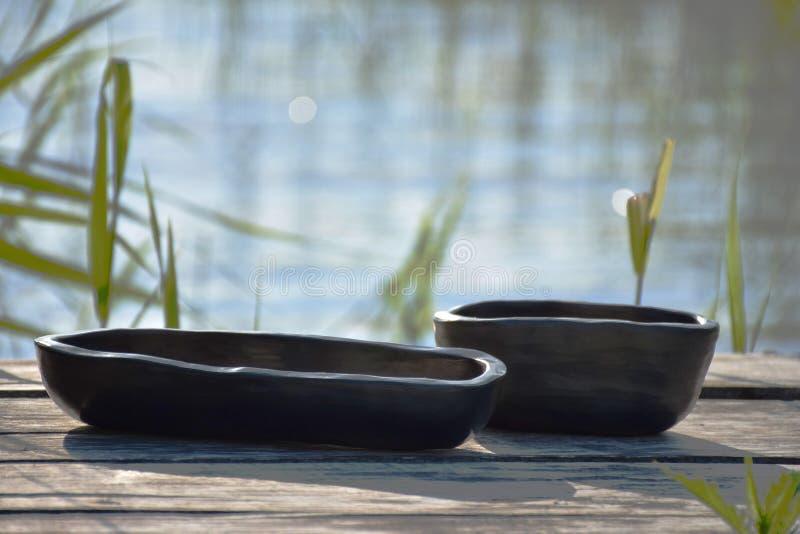 与独特的手工制造黑瓦器盘特写镜头的夏天心情在早晨阳光下 免版税库存图片