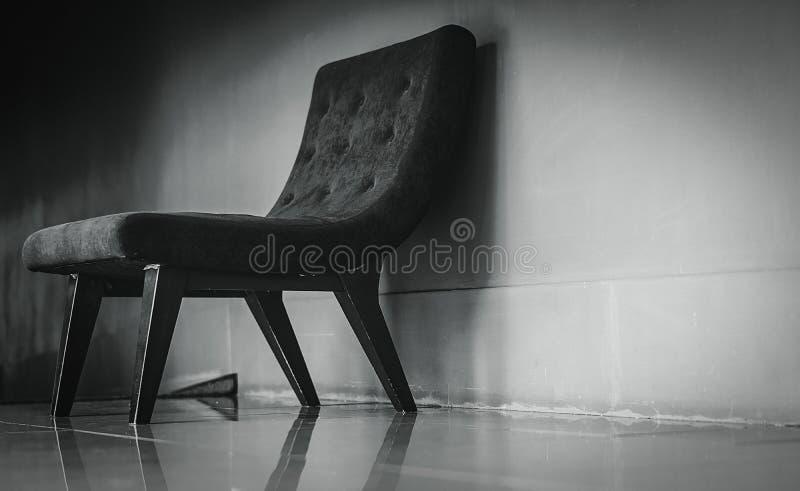与独特的设计的黑经典椅子在混凝土墙附近的空的休息室在黑暗和剧烈的背景 一把空的扶手椅子 库存照片
