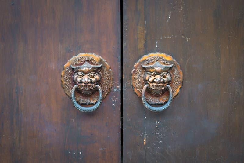 与狮子通道门环的木门细节关闭,亚洲 寺庙中国风格建筑学  库存图片