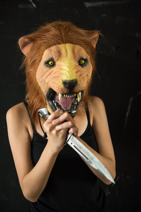 与狮子面具的女性凶手与刀子 库存图片