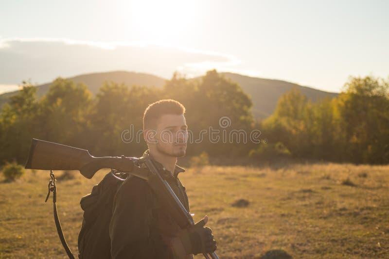 与猎枪枪的猎人在狩猎 寻找设备待售 山狩猎 库存图片