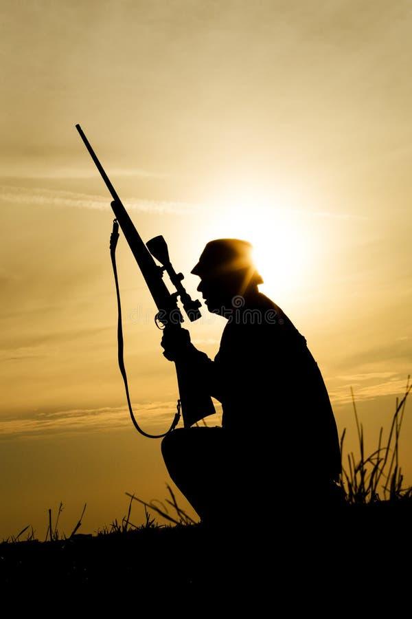 与猎枪的猎人在日落 免版税库存图片