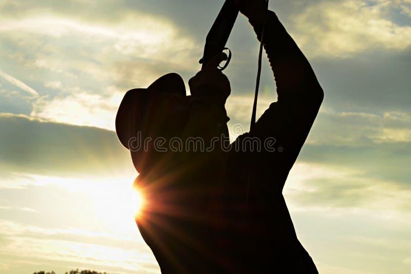 与猎枪的猎人射击,反对日落的剪影 图库摄影