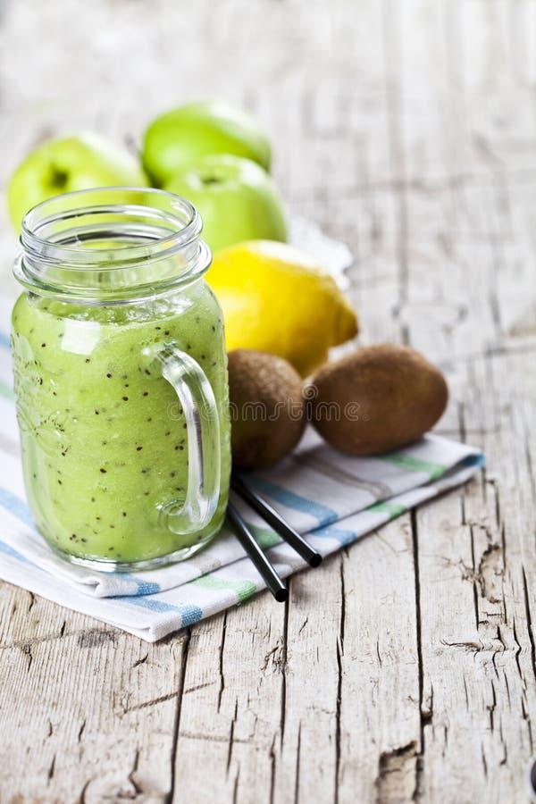 与猕猴桃、苹果、柠檬和chia种子的绿色圆滑的人 吃健康新的饮食,superfood 免版税库存照片
