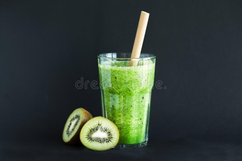 与猕猴桃的健康绿色圆滑的人在黑背景的一玻璃杯 图库摄影