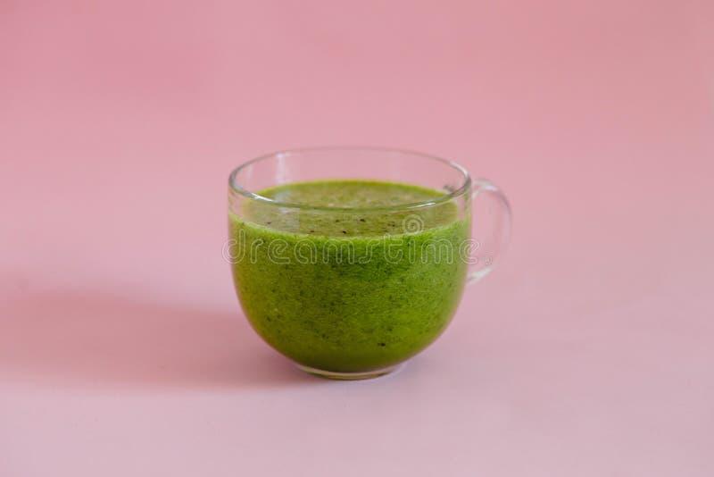 与猕猴桃的健康绿色在一个玻璃杯子的圆滑的人和苹果在桃红色背景 免版税库存图片