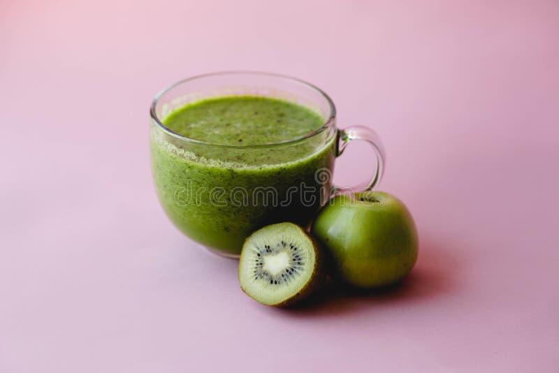 与猕猴桃的健康绿色在一个玻璃杯子的圆滑的人和苹果在桃红色背景 库存照片