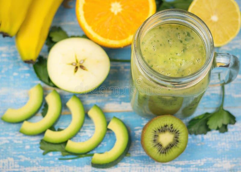 与猕猴桃的鲕梨圆滑的人、桔子和一个猕猴桃的香蕉和一半在蓝色木桌上的 饮食素食主义者食物 未加工的食物 免版税图库摄影