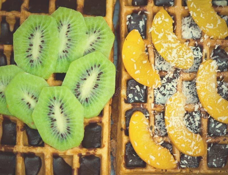 与猕猴桃的比利时华夫饼干,桔子 椰子剥落和巧克力,自创健康早餐,选择聚焦 库存图片
