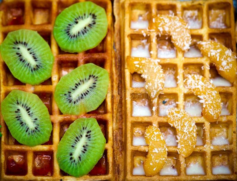 与猕猴桃的比利时华夫饼干,桔子 椰子剥落和巧克力,自创健康早餐,选择聚焦 库存照片