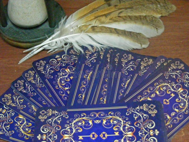 与猫头鹰羽毛和滴漏关闭的占卜用的纸牌 免版税库存照片