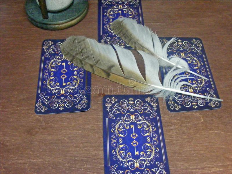 与猫头鹰羽毛的在棕色背景的占卜用的纸牌和滴漏 免版税库存照片
